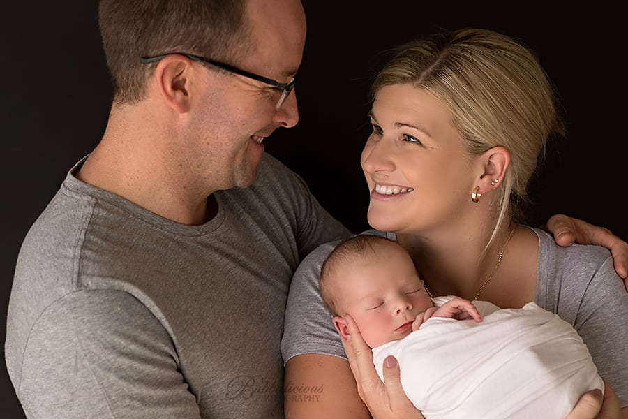 Mum and dad smile at each other while holding newborn - Sunshine Coast Gympie Newborn Photographer
