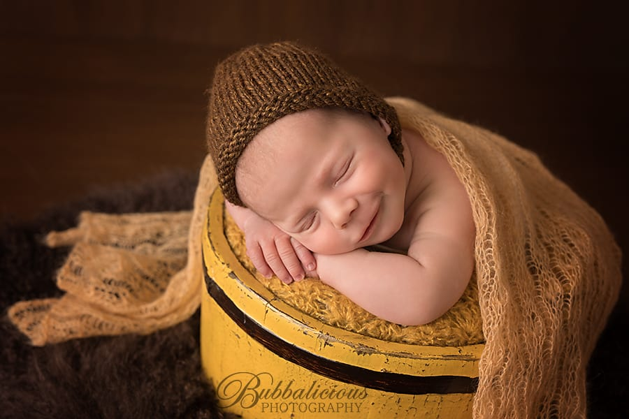 Newborn posed in a yellow bucket with a cheeky grin - Sunshine Coast Gympie Newborn Photographer