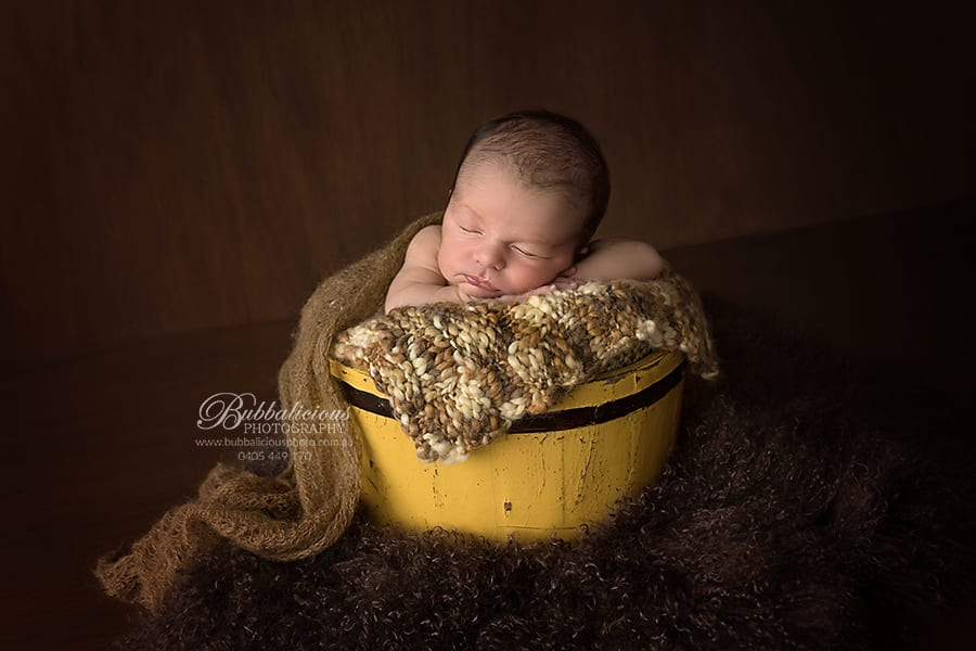Newborn posed in an antique yellow bucket - Sunshine Coast Gympie Newborn Photographer