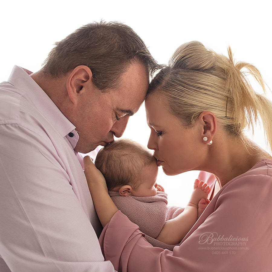 The newborn could not be any more loved with kisses from Mum and Dad - Sunshine Coast Gympie Newborn Photographer