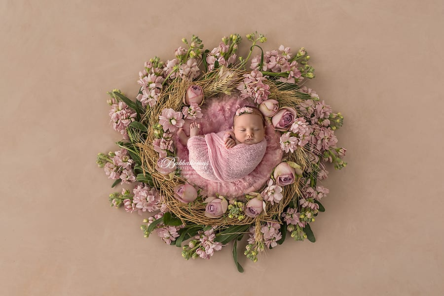 Wrapped newborn in pink posed on a floral nest - Sunshine Coast Gympie Newborn Photographer