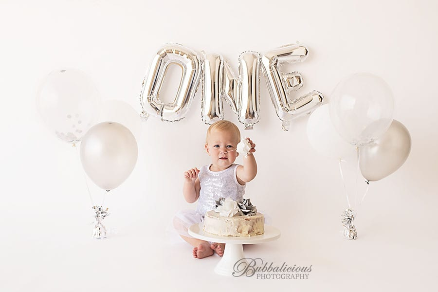 Toddler with her first birthday cake and balloons - Sunshine Coast Gympie Baby Photographer