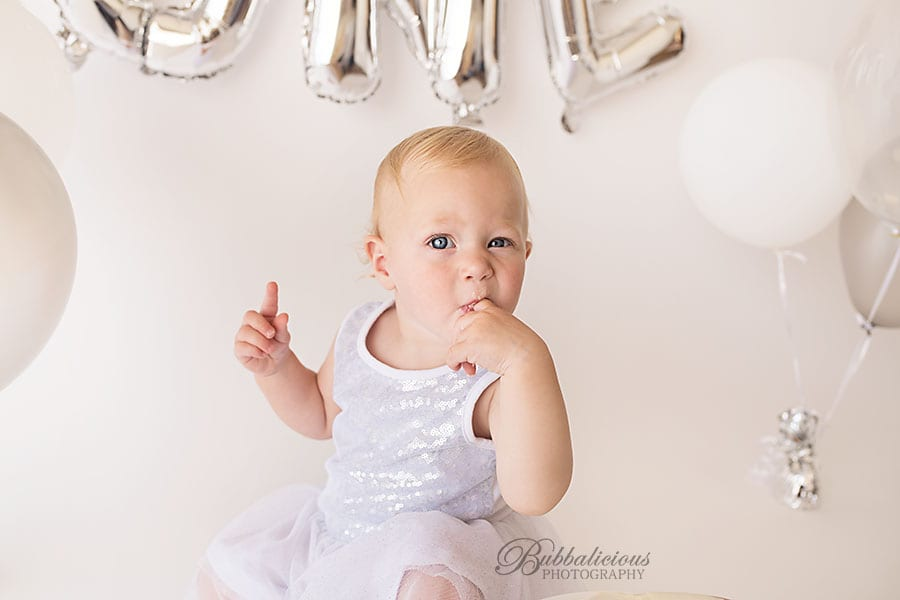 Liking fingers after eating first birthday cake - Sunshine Coast Gympie Baby Photographer