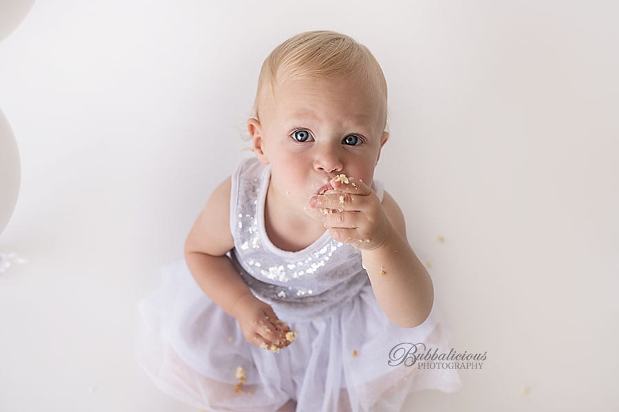Toddler girl tasting her first birthday cake - Sunshine Coast Gympie Baby Photographer