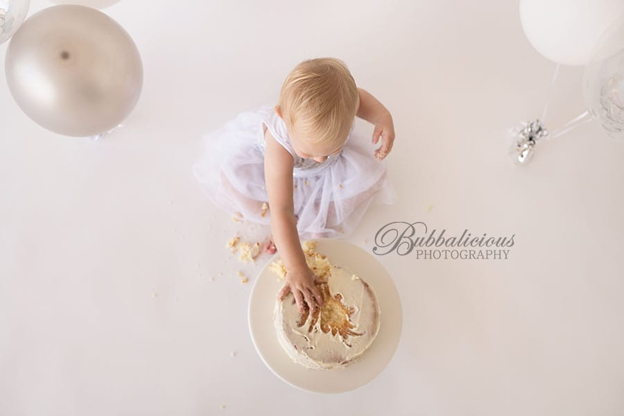 Toddler girl attacking her first birthday cake - Sunshine Coast Gympie Baby Photographer