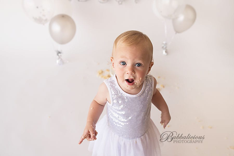 Toddler girl with cake all over face and hands, on her first birthday - Sunshine Coast Gympie Baby Photographer