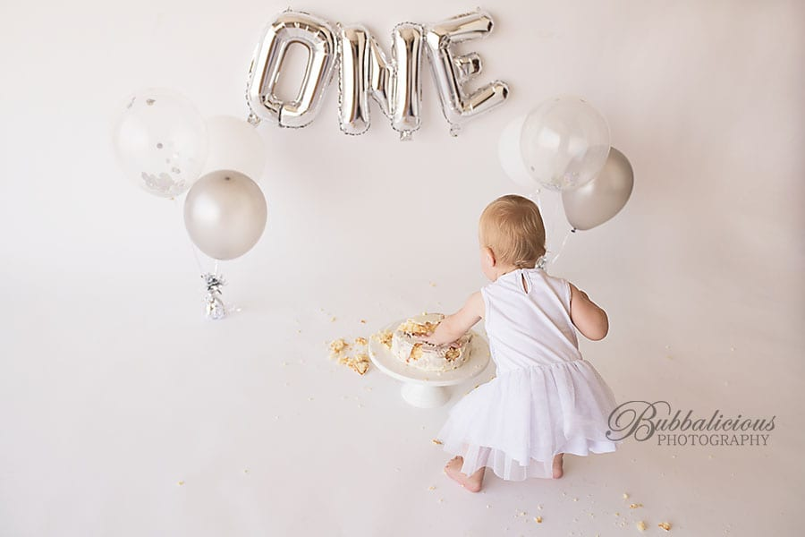 Toddler girl having fun with a birthday cake and balloons - Sunshine Coast Gympie Baby Photographer