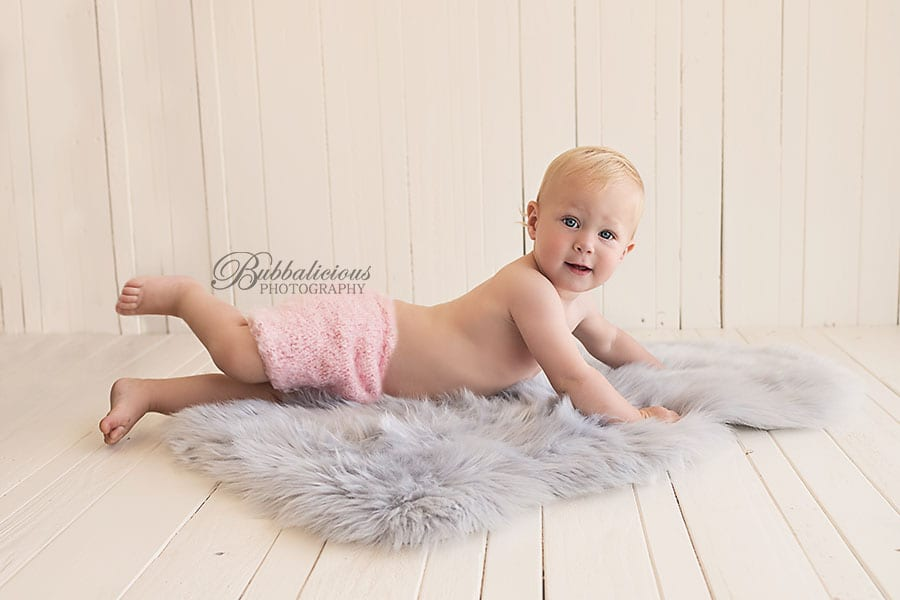 Toddler in pink knit pants laying on lambswool rug - Sunshine Coast Gympie Baby Photographer
