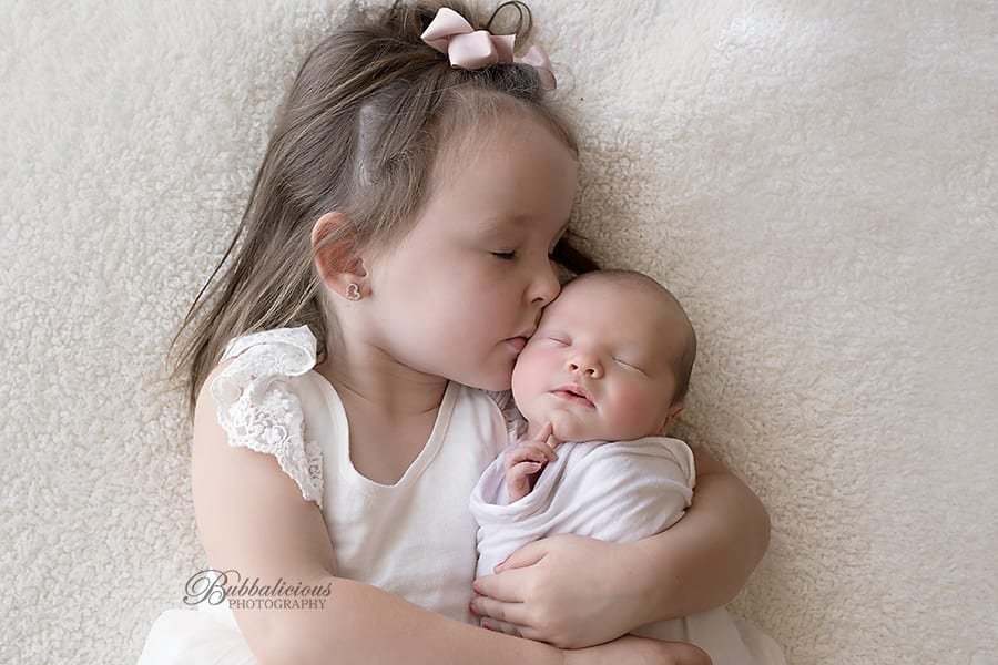 Young girl hugging and kissing her baby sister - Sunshine Coast Gympie Newborn Photographer