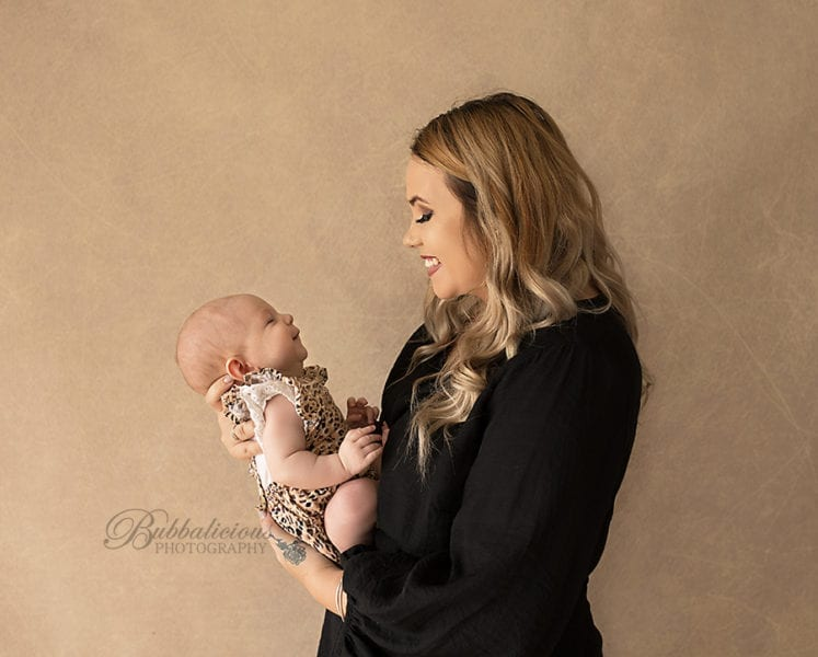 Mum holding her new baby and looking lovingly at her - Sunshine Coast Gympie Newborn Photographer