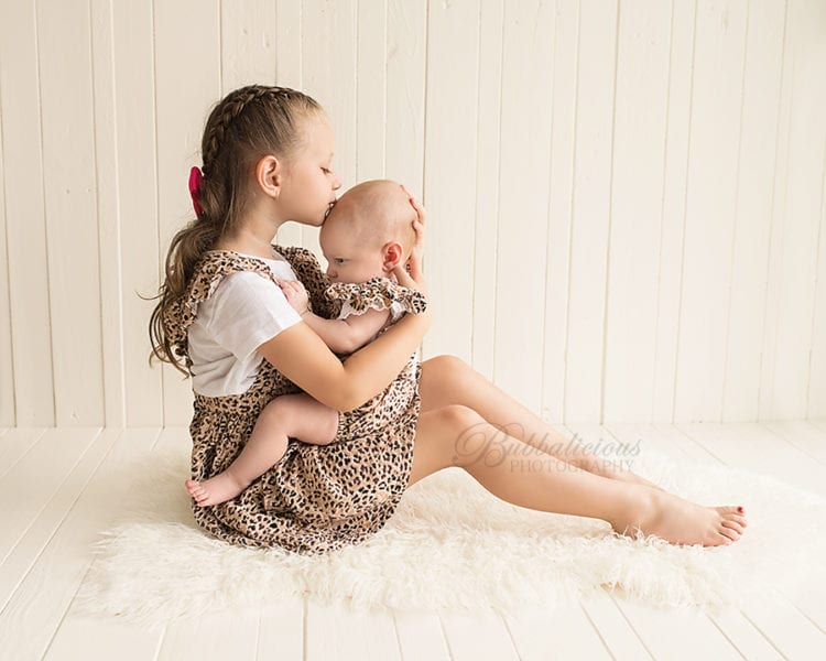 Big sister hugging and kissing new baby on the head - Sunshine Coast Gympie Newborn Photographer