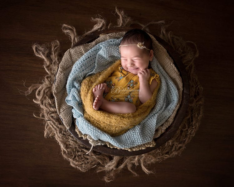 A grinning newborn wrapped in a rustic pose - Sunshine Coast Gympie Newborn Photographer