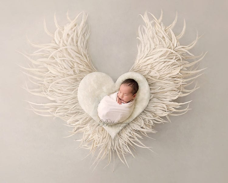Wrapped newborn posed on angelic feathered heart - Sunshine Coast Gympie Newborn Photographer