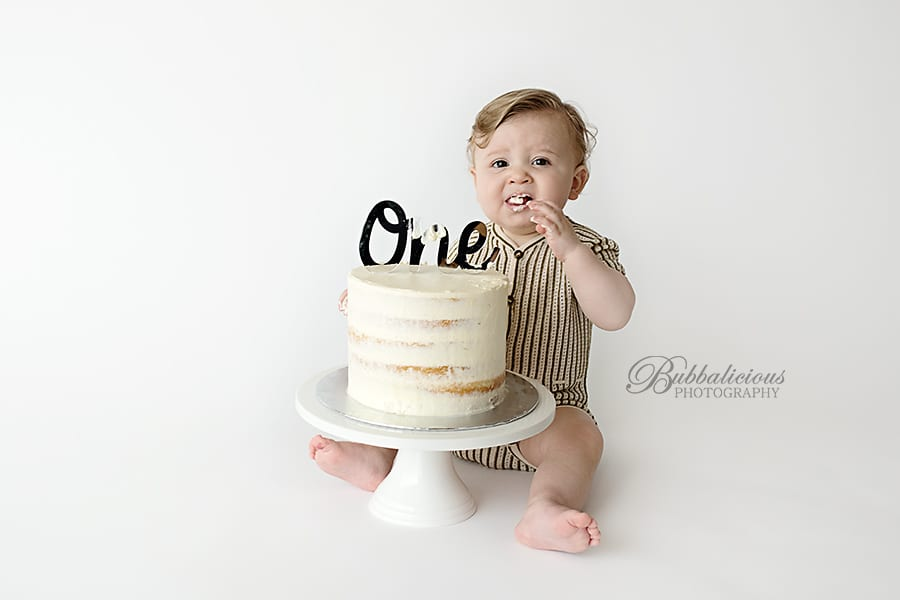 A baby boy turning one eating cake - Sunshine Coast Gympie Baby Photographer