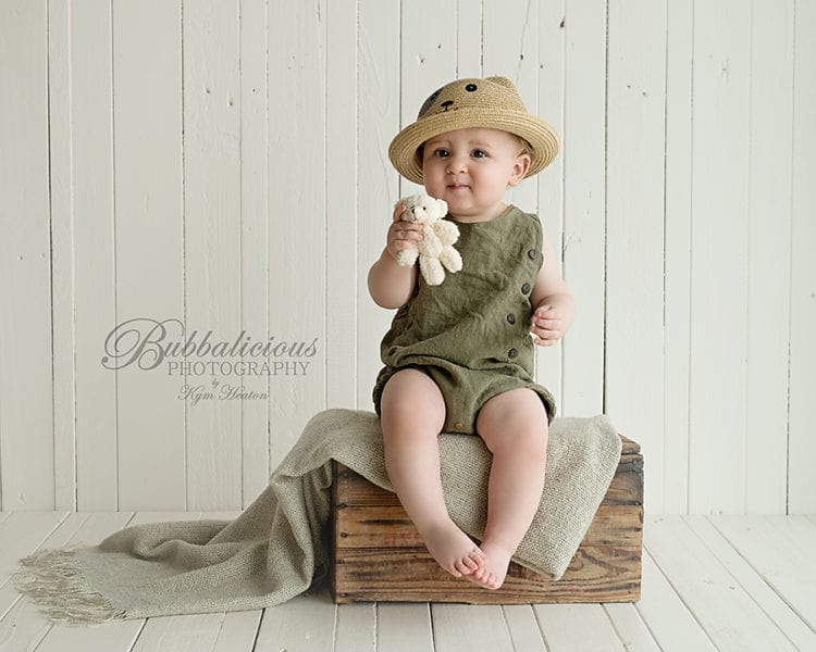 Baby boy wearing a cool hat sitting on an antique crate - Sunshine Coast Gympie Baby Photographer