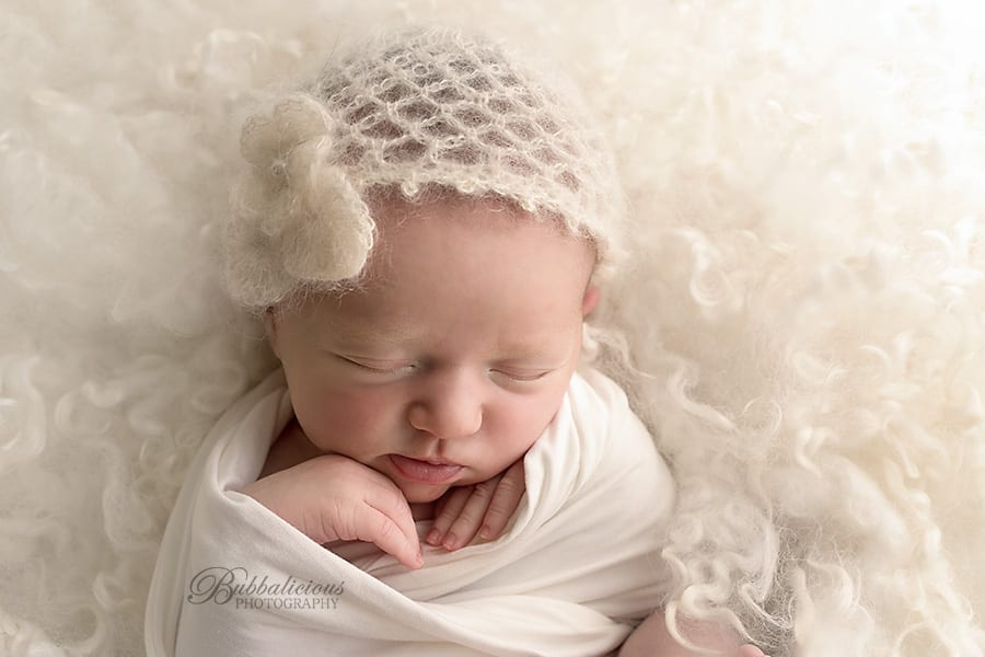 Close up of baby girl with a white bonnet on - Sunshine Coast Gympie Newborn Photography