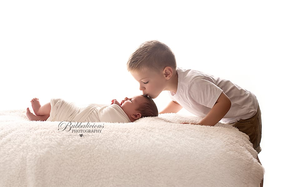 Big brother kissing his baby sister backlit - Sunshine Coast Gympie Newborn Photography